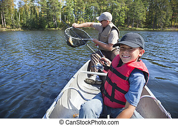 Young boy fisherman smiles at catch of nice walleye - Young...
