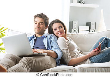 Couple surfing the net at home - Young couple relaxing on...