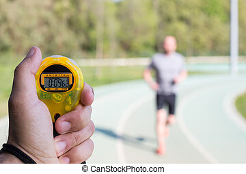 Timing times - Coach clocking times in a running track