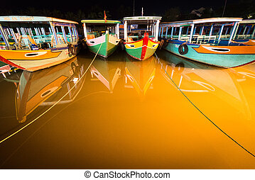 Boats at night in Hoi An, Vietnam, Asia - Wooden boats of...