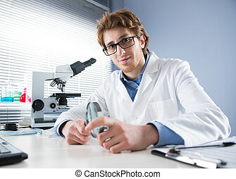 Chemical laboratory technician holding magnifier - Chemical...