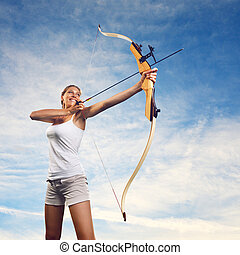 Woman practicing with bow and arrow - Attractive woman...