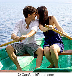Italian couple on wood boat rowing and kissing - Happy...