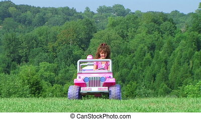Girl Driving Toy Jeep - Girl driving toy jeep in grass.
