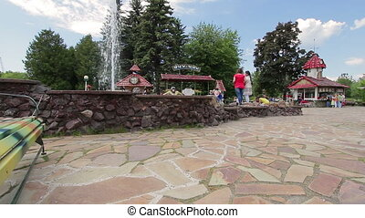 Fountain in amusement park and vacationers people