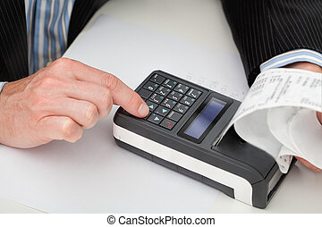 Cash register and receipt - A man working on a small modern...