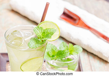 Iced green tea with lime garnish and ice cube