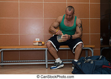 Bodybuilder Eating Healthy Diet Food Out Of Tupperware -...