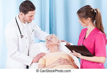 Doctors and elderly patient - Two doctors taking elderly...