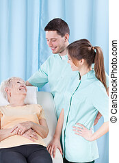 Elderly woman talking to doctors - Elderly woman lying on...