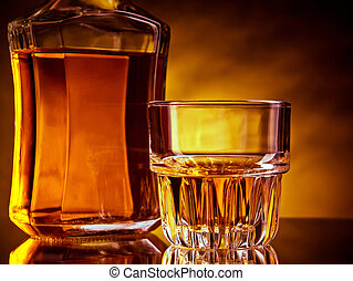 Whiskey - Glass and a bottle of whisky against red and...