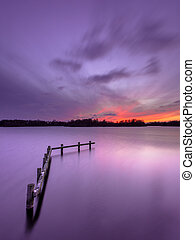 Purple Sunset over Tranquil Lake with Wooden Mooring Post -...