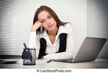 tired young business woman with laptop computer at the office
