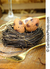 Easter eggs in the nest and golden fork on wooden background