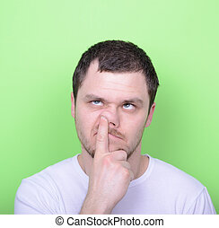 Portrait of a young man with his finger in his nose against...