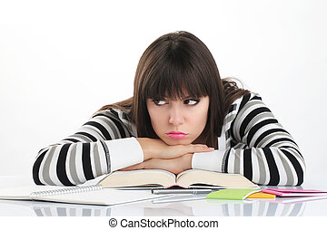 beautiful girl studying sitting at the table with books and...