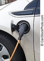 electric car - charging an electric car at a charging...