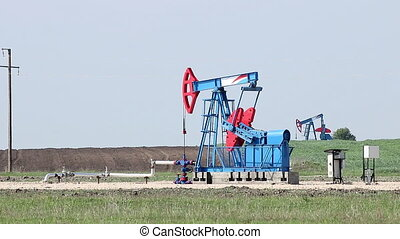 two oil pump jack on field