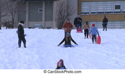 Teenagers Sled Riding - Teenagers sledding down hill and...