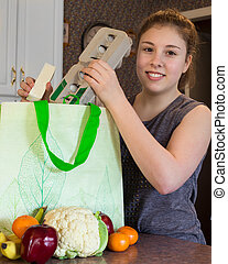 Girl with grocery bag - Cute girl unpacking healthy...