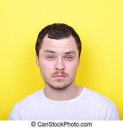 Portrait of man with funny face against yellow background -...