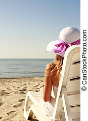 girl in hat is lying on a deck chair on the beach - a girl...