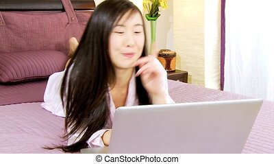 Asian woman at home chatting in bed
