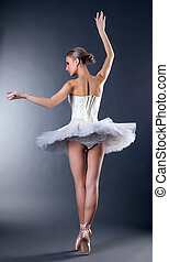 Rear view of graceful young ballerina dancing on tiptoe