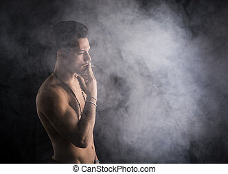 Shirtless young man smoking cigarette with a lot of smoke...