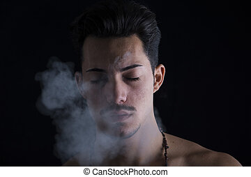 Attractive young man smoking, eyes closed - Attractive young...
