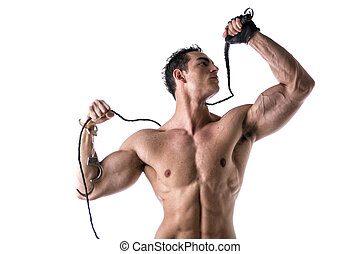 Muscular shirtless young man with handcuffs, whip and glove...