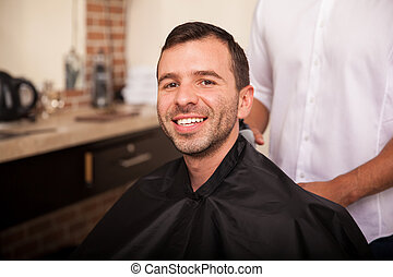 Happy customer in a barber shop - Handsome young man getting...