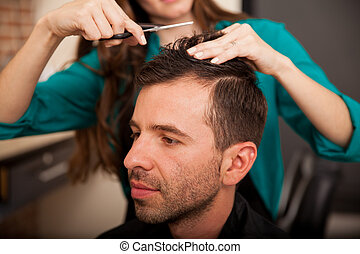Young man getting a haircut - Portrait of a young Hispanic...