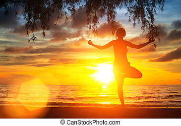 Yoga tree pose by woman silhouette with sunset sky...