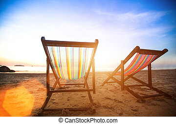 Perfect vacation concept, pair of beach loungers on the deserted coast sea at sunrise.