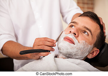 Getting a close shave - Closeup of a young man getting a...