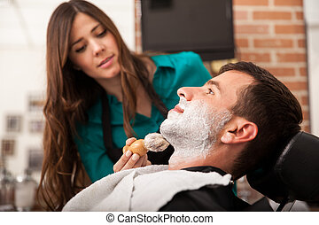 Female barber shaving a man - Profile view of a young man...