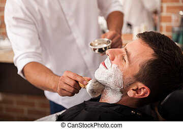 Ready for a shave at the barber's - Barber putting some...