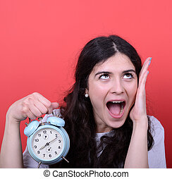 Portrait of girl screaming while holding clock against red...
