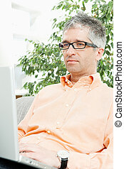 Man browsing internet - Mid-adult man wearing jeans and...