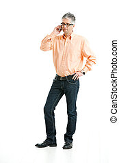 Man talking on mobile phone - Grey haired man wearing jeans...
