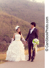 Wedding - Cheerful married couple standing on the nature and...