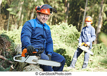 Lumberjack worker with chainsaw in the forest - Portrait of...