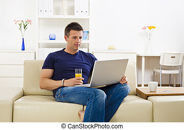 Man using laptop computer - Man sitting on sofa at home and...