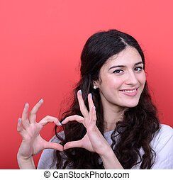 Portrait of happy woman making heart shape with hands...