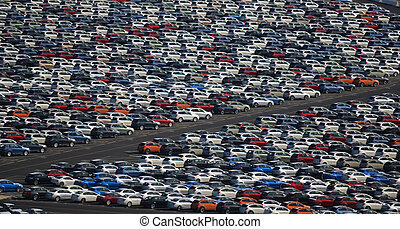 New Cars Parked in a Lot - New cars, just off a cargo ship,...