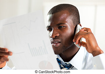 businessman examining documents - young adult afro-american...
