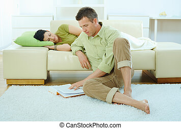 Man reading book at home - Young couple resting at home. Man...