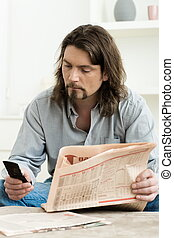 Man using mobile phone and holding newspaper in hand,...