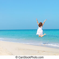 Woman in white dress jumping on the beach